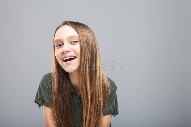有括号笑的美丽的微笑女孩 免版税库存图片