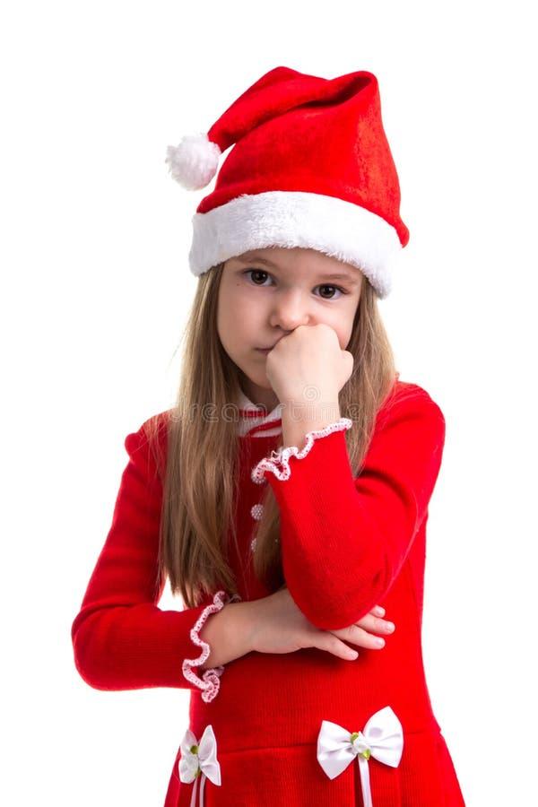 有拳头的哀伤的圣诞节女孩在下巴下,看平直,戴圣诞老人帽子被隔绝在白色背景 免版税库存照片