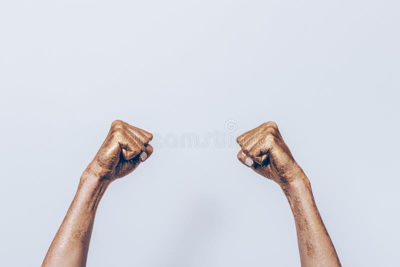 有拳头的金黄女性手 库存照片