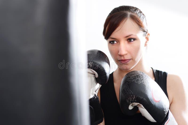 有拳击手套和沙袋的少妇 免版税库存照片