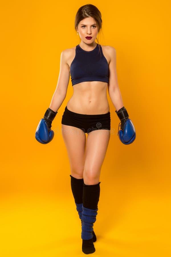 有拳击手套摆在的美丽的体育女孩 免版税库存图片