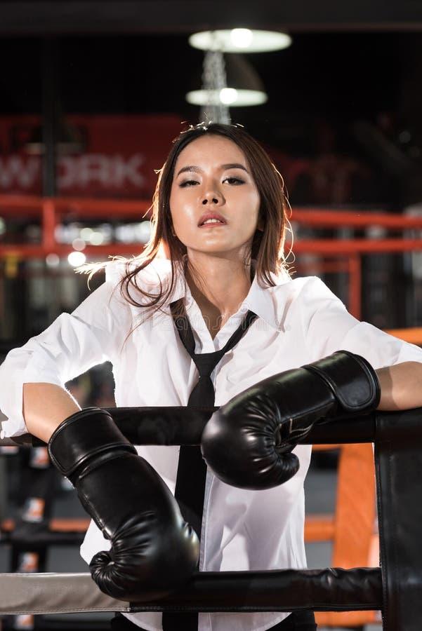 有拳击手套的,疲倦年轻亚裔女实业家 库存照片