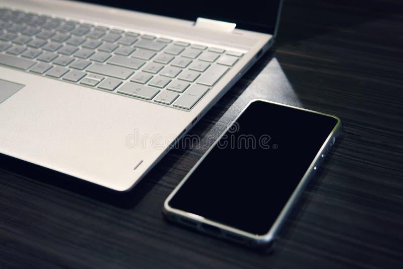 有拷贝空间屏幕和膝上型计算机的智能手机在木桌背景 流动左边的空的黑屏幕在的 库存图片