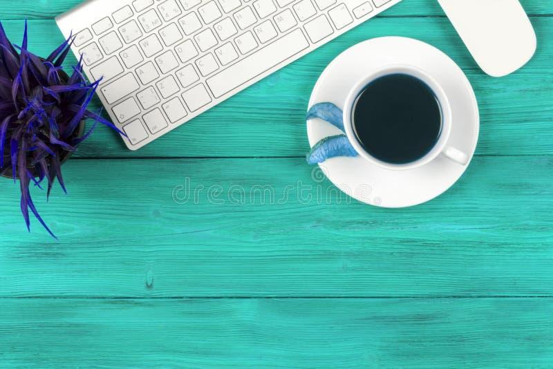 有拷贝空间的办公桌 数字式设备无线键盘和老鼠在蓝色木桌上与杯子新鲜的咖啡,顶视图 免版税图库摄影