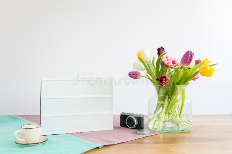 有拷贝空间的在木书桌上的灯箱和花有白色的 图库摄影