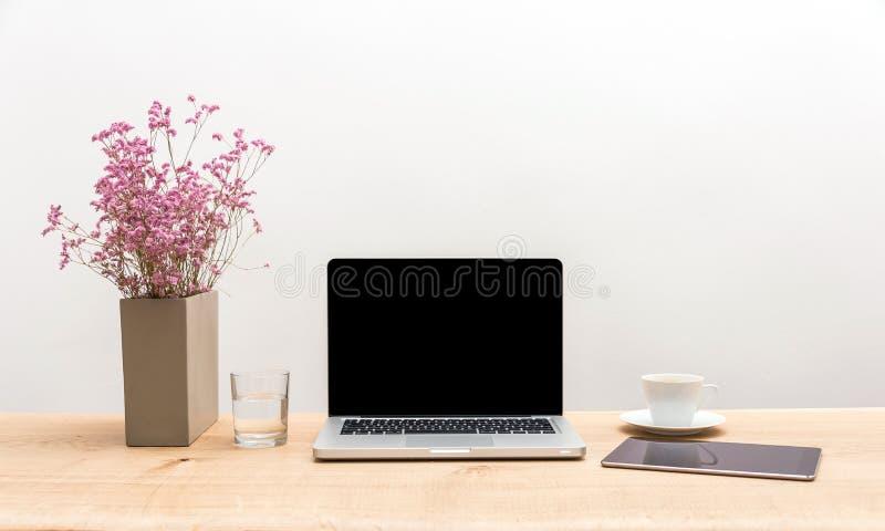 有拷贝空间的在木书桌上的膝上型计算机和片剂有白色后面的 免版税库存照片