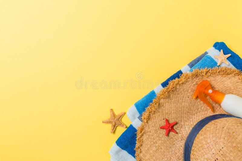 有拷贝空间的海滩平的被放置的辅助部件 镶边的蓝色和白色毛巾、贝壳、staw sunhat和一个瓶sunblock  免版税库存图片