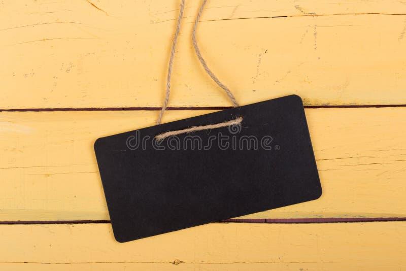 有拷贝空间的黑布告牌在木背景 免版税库存照片