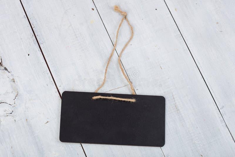 有拷贝空间的黑布告牌在白色木头 免版税库存图片