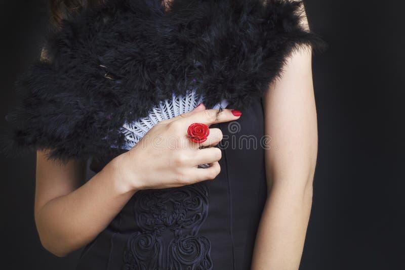 有拿着一个黑爱好者的一个红色圆环的女性手 黑礼服的妇女在黑背景 免版税库存照片
