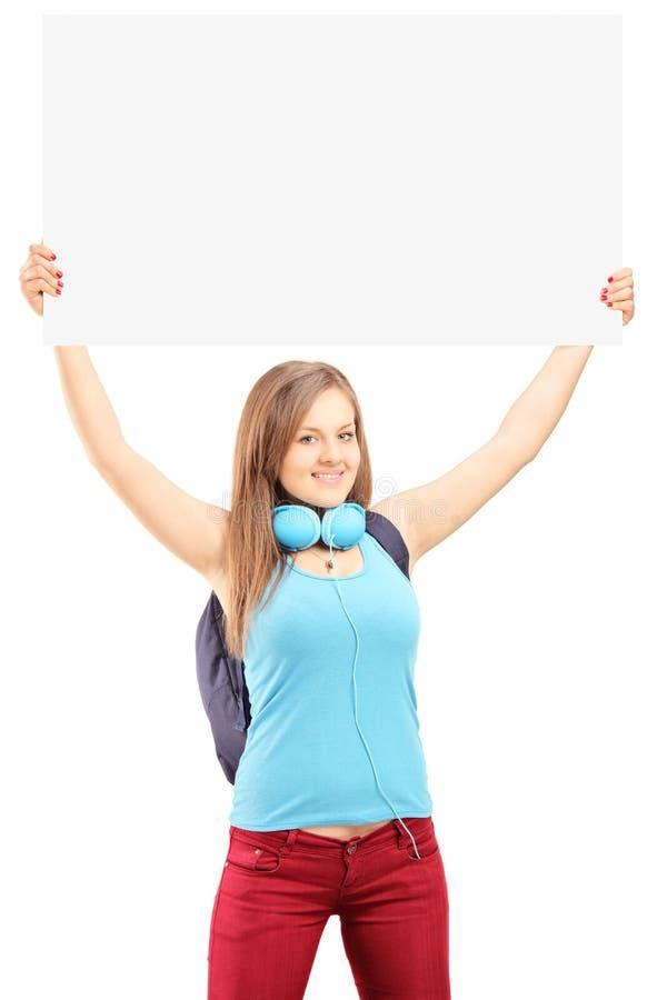 有拿着一块白色单块玻璃的学校背包的美丽的年轻女性 免版税库存图片