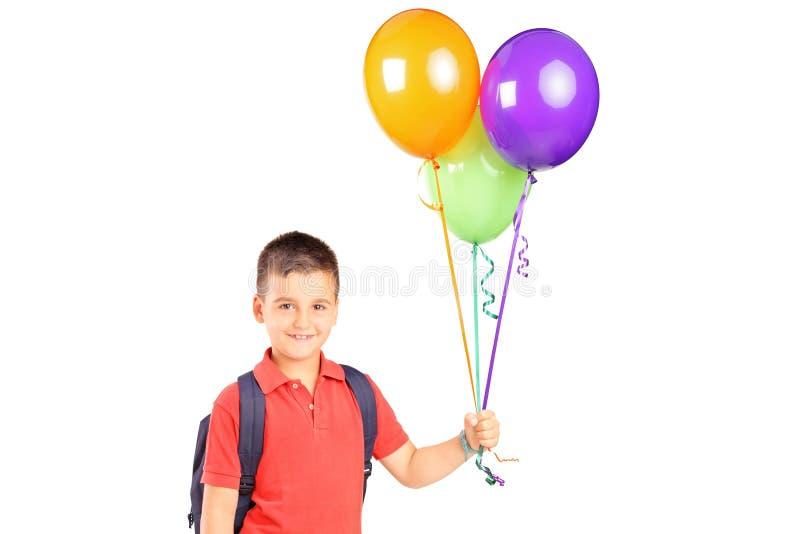 有拿着一束气球的袋子的男小学生 免版税库存图片