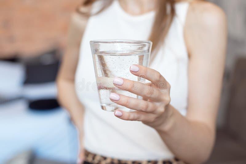 有拿着一杯水,后方veaw的亭亭玉立的身体的特写镜头妇女 免版税库存照片
