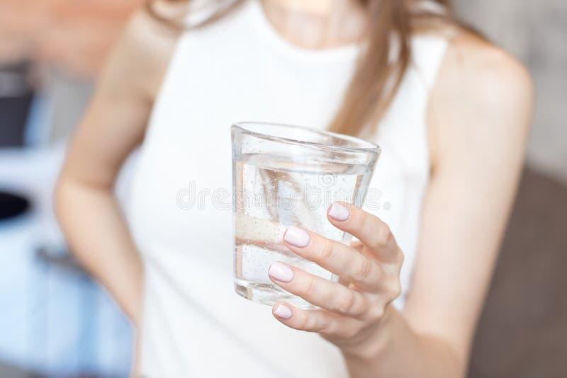有拿着一杯水,后方veaw的亭亭玉立的身体的特写镜头妇女 免版税图库摄影