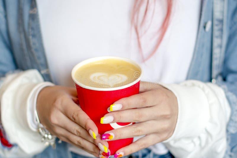 有拿着一杯红色咖啡与被绘的心脏的明亮的夏天修指甲的手女孩 免版税库存照片