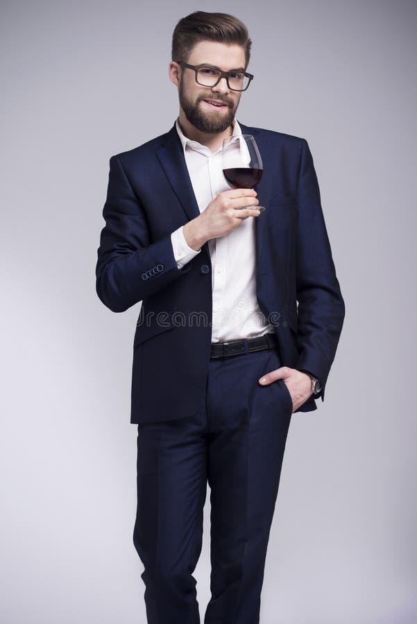 有拿着一杯酒的胡子的英俊的人在他的手上 免版税库存照片