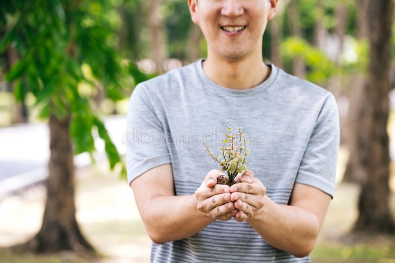 有拿着一棵小小的树的微笑的年轻愉快的亚裔男性志愿者准备好是在土壤的装壶 免版税库存照片