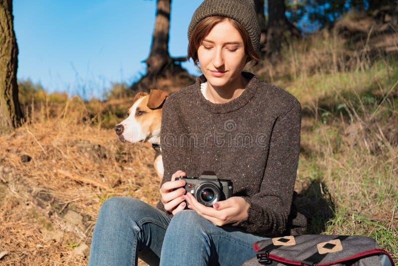 有拿着一胶卷相机的狗的妇女在美好的秋天天 年轻f 免版税图库摄影