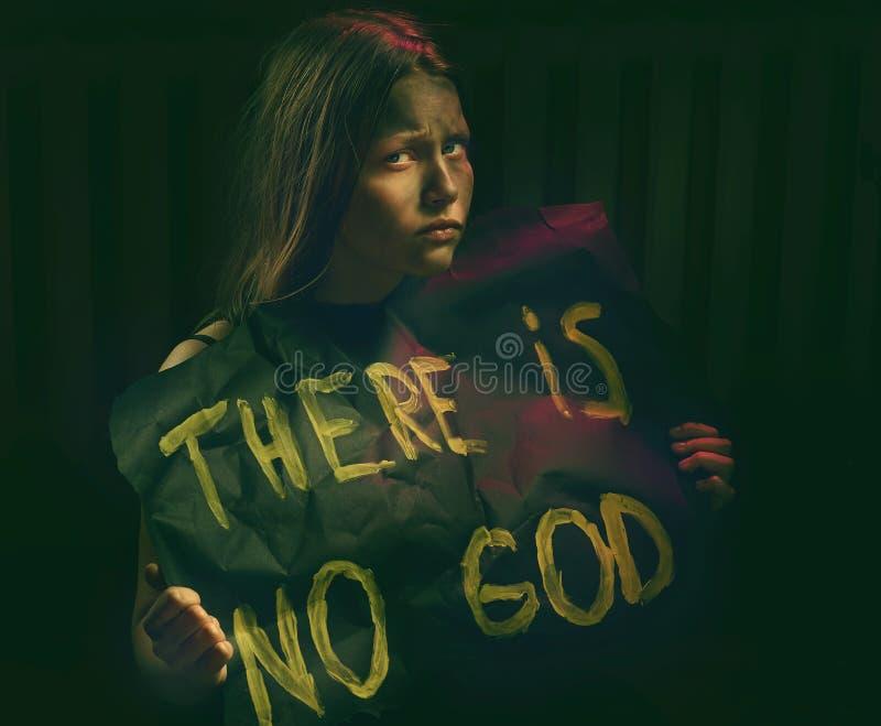 有拿着与文本的肮脏的面孔的青少年的女孩横幅-没有上帝 免版税库存图片
