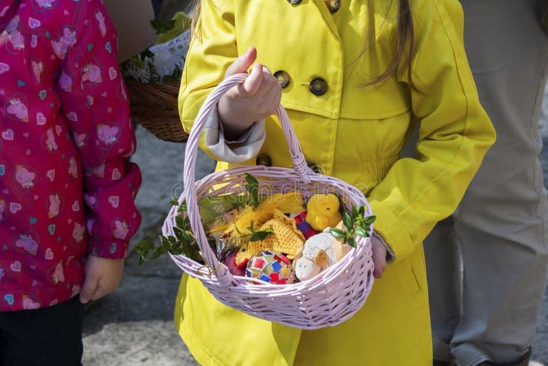 有拿着与自创装饰、鸡蛋和准备的食物的父母的一个孩子一个传统擦亮剂复活节篮子 库存图片