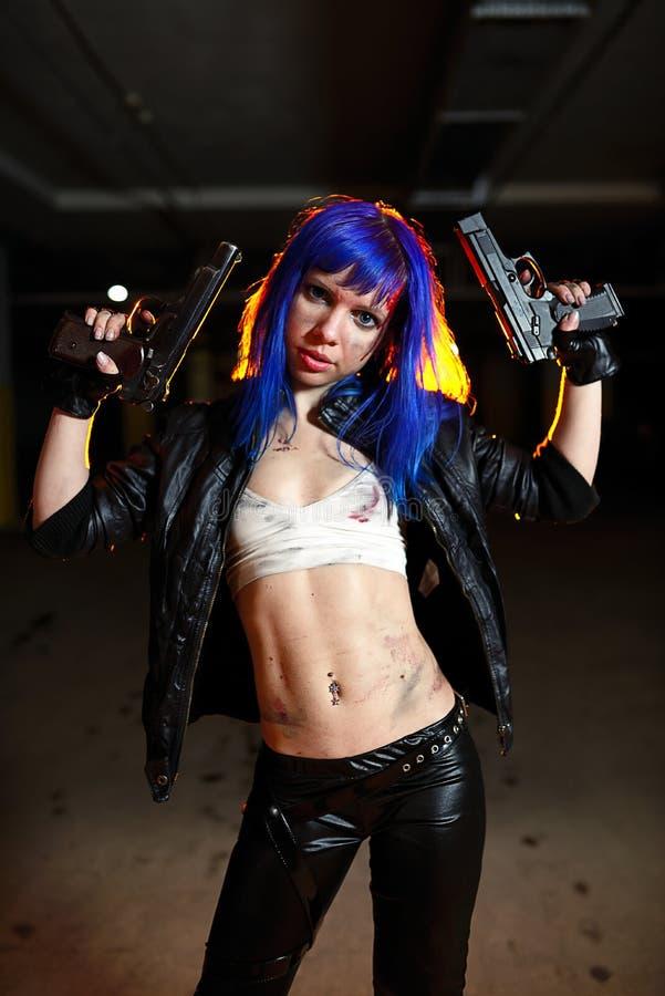 有拿着两杆枪和看作为凶手的蓝色头发的性感的妇女 免版税库存照片