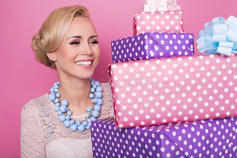 有拿着五颜六色的礼物盒的大美好的微笑的妇女 颜色箭深度域浅软件 圣诞节,生日,情人节,提出 免版税图库摄影
