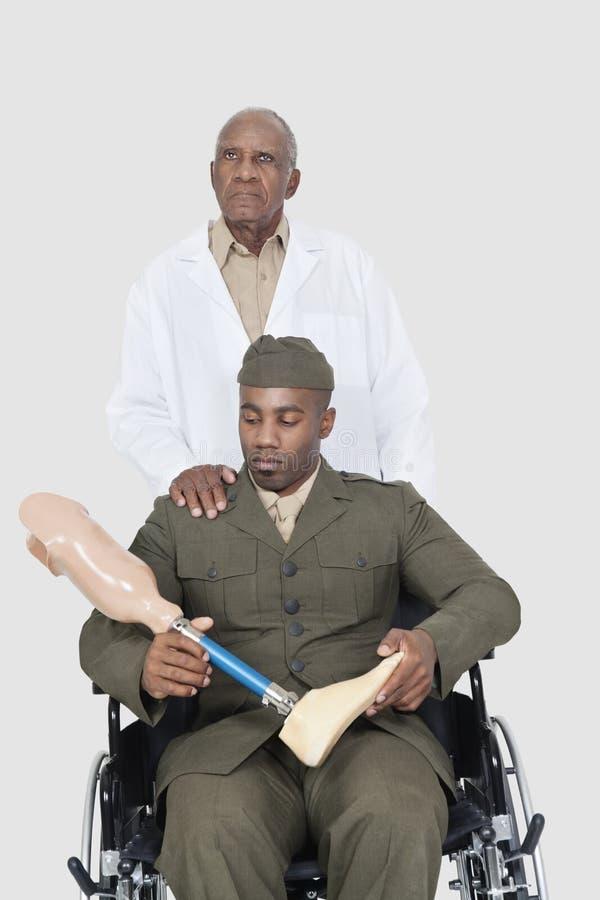 有拿着人为肢体的美军官员的资深医生,他在灰色背景的轮椅坐 免版税库存图片