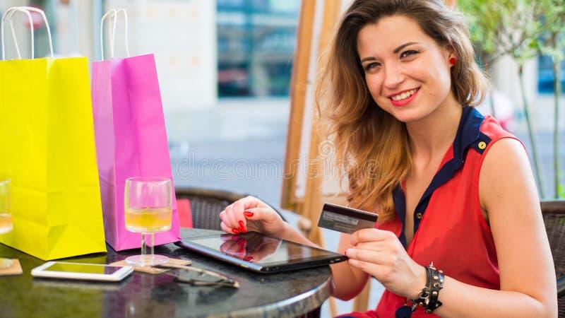 有拿着信用卡的垫的年轻俏丽的妇女。她在咖啡馆选址。 库存照片