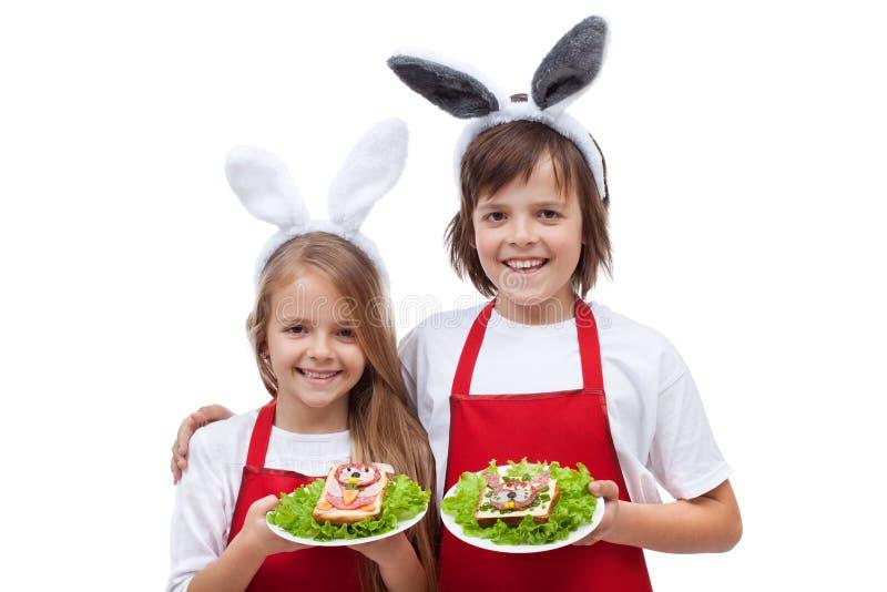 有拿着兔子的兔宝宝耳朵的愉快的厨师塑造了三明治 免版税库存照片