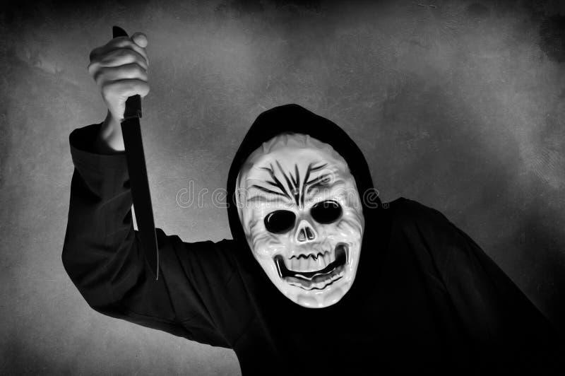 有拿着刀子的一个人的头骨面具的妇女 库存图片
