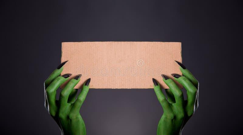 有拿着卡片的空的片断黑钉子的绿色妖怪手 免版税图库摄影