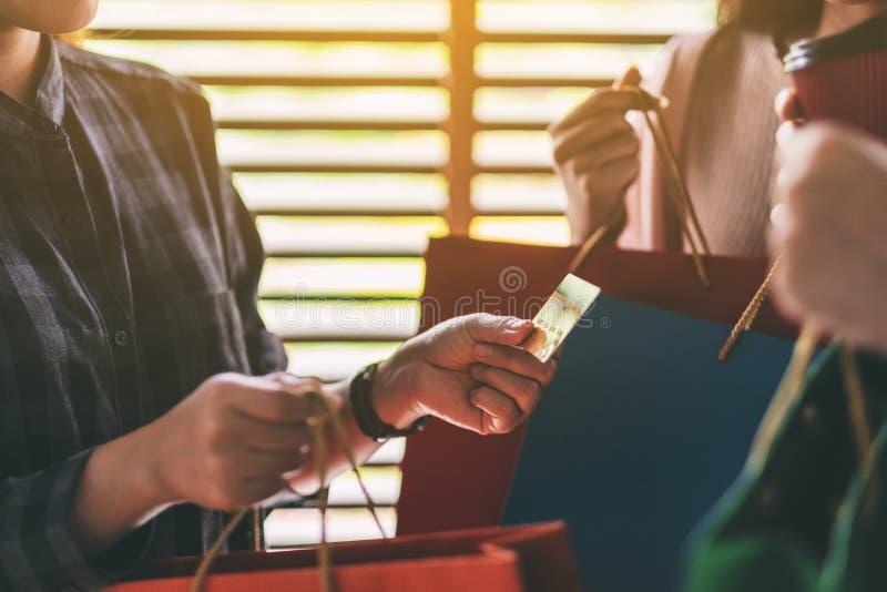 有拿着和使用信用卡的购物带来的人们为购买 免版税库存图片