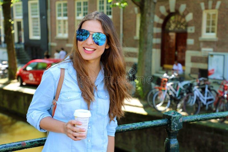 有拿着咖啡的飞行员太阳镜的微笑的年轻都市妇女室外在阿姆斯特丹中心,荷兰,欧洲 库存照片