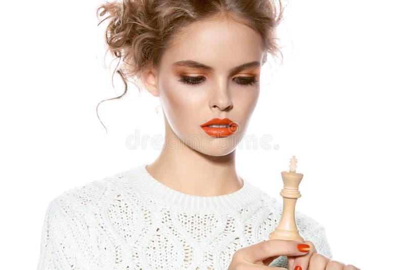 有拿着国王棋子的晚上构成的美丽的妇女 免版税库存图片
