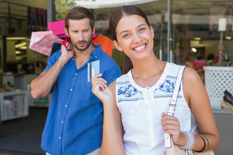 有拿着在她后的一个有关人的年轻愉快的妇女购物袋 免版税图库摄影