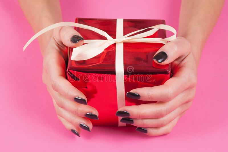 有拿着在桃红色背景的黑钉子的年轻女性手红色当前箱子 免版税库存照片