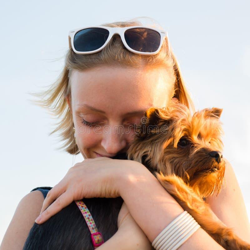 有拿着小狗的金发的美丽的年轻愉快的妇女 免版税图库摄影
