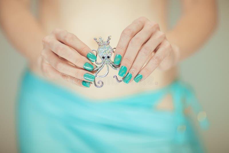 有拿着小的章鱼别针,愉快的比基尼泳装海滩心情的完善的蓝色指甲油的美好的妇女手 免版税图库摄影