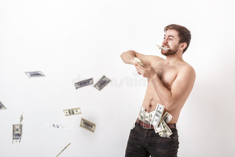 有拿着很多一百元钞票的胡子的年轻英俊的人和投掷他们入空气 货币和财富 免版税图库摄影
