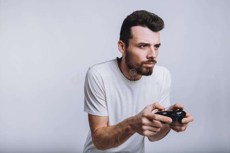 有拿着控制杆的胡子的假装年轻的人他打比赛 免版税库存图片