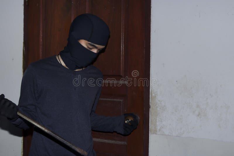 有拿着撬杠的巴拉克拉法帽的被掩没的夜贼对闯入房子在夜间 砖概念罪行前面现有量苛刻的藏品手枪影子墙壁 免版税库存图片
