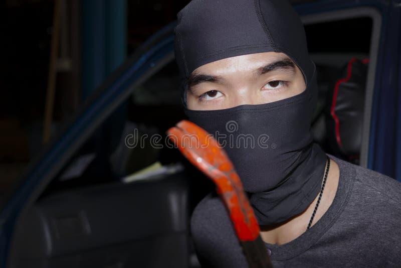有拿着撬杠的巴拉克拉法帽的被掩没的窃贼对闯进汽车 砖概念罪行前面现有量苛刻的藏品手枪影子墙壁 库存照片