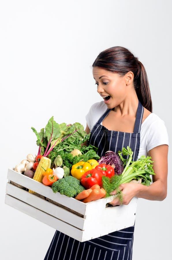 有拿着新鲜的地方有机产物的围裙的微笑的厨师 免版税图库摄影