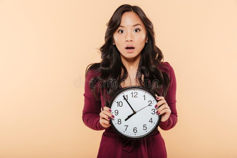 有拿着时钟的卷曲长的头发的年轻亚裔妇女显示nea 库存图片