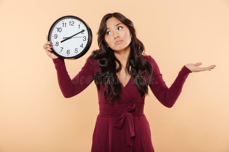 有拿着时钟showin的卷曲长的头发的困惑的深色的妇女 库存图片