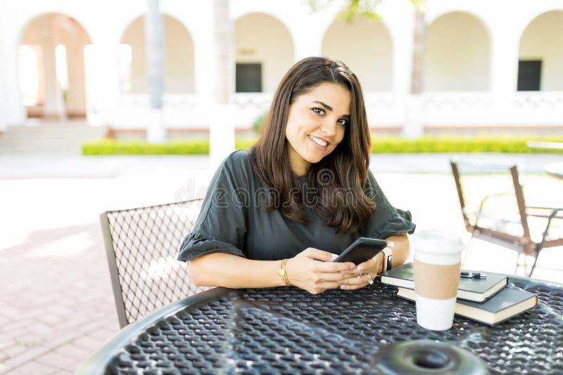有拿着智能手机的美好的微笑的妇女在表上 库存图片