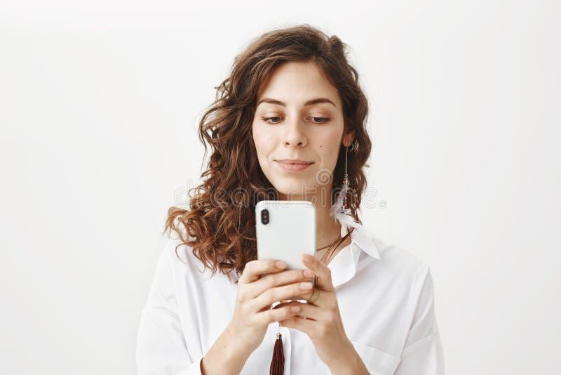 有拿着智能手机,当传讯或打比赛时的卷发的被吸引的和正面肉欲的白种人妇女 免版税库存照片