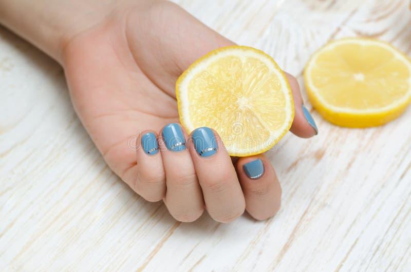 有拿着柠檬的浅兰的钉子艺术的女性手 免版税库存图片