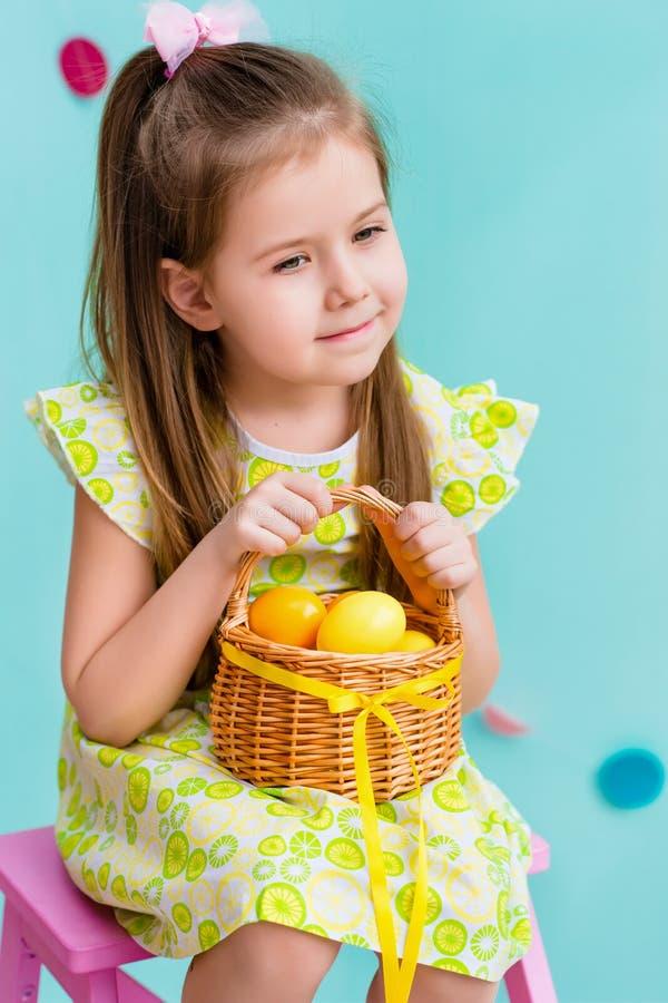 有拿着柳条筐用黄色鸡蛋的长的金发的体贴的小女孩 库存图片