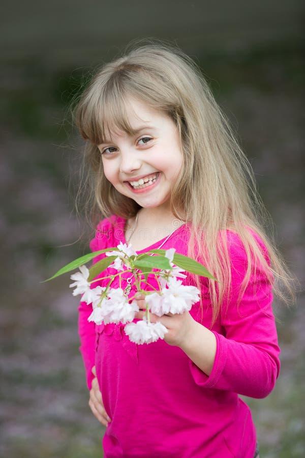 有拿着桃红色佐仓开花的微笑的面孔的小女婴 免版税图库摄影